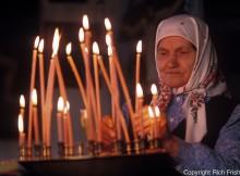 Photograph of elderly Russian woman in a babushka lighting prayer candles in a Russian Orthodox church in Russian Far East City of Sovetskaya Gavan ©Rich Frishman